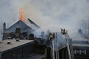 Flames leap out of the roof space of the Glasgow School of Art Mackintosh building in 2014. The internationally acclaimed building was saved from total destruction by a dedicated team of firefighters.<br /> <br /> © John Linton<br /> All rights reserved