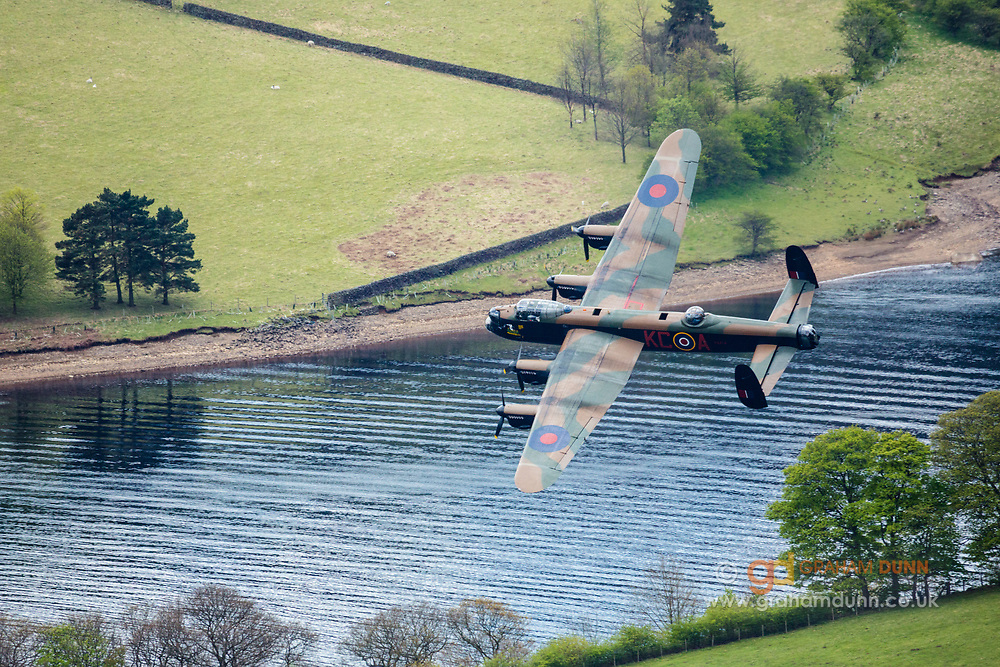 An RAF Lancaster Bomber plane flies over Ladybower Reservoir in the Upper Derwent Valley as part of the Dambusters 617 Squadron 70th Anniversary Commemorative Flypast. May 16th 2013. Derbyshire, Peak District.