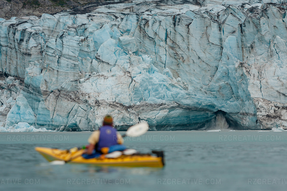 A view of Lamplugh Glacier in southeast Alaska as a woman paddles a yellow sea kayak in the foreground. Photo © Robert Zaleski / rzcreative.com<br /> —<br /> To license this image contact: robert@rzcreative.com