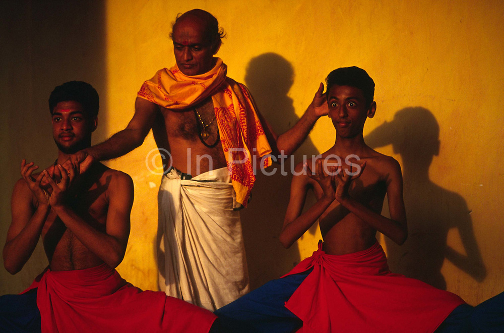 Professor Balasubramanian guides his students in the correct position for a role. Kerala Kalamandalam.The Kalamandalam was founded in the 1930's to preserve the ancient forms of Keralan arts and dance of which Kathikali, a mute mixture of ballet and drama is the most well known..Cherathuruty, Kerala, India
