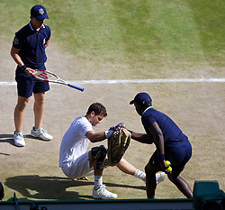 04.07.2014, All England Lawn Tennis Club, London, ENG, ATP Tour, Wimbledon, im Bild Grigor Dimitrov (BUL) is helped up by a ball-boy during the Gentlemen's Singles Semi-Final match on day eleven // during the Wimbledon Championships at the All England Lawn Tennis Club in London, Great Britain on 2014/07/04. EXPA Pictures © 2014, PhotoCredit: EXPA/ Propagandaphoto/ David Rawcliffe<br /> <br /> *****ATTENTION - OUT of ENG, GBR*****