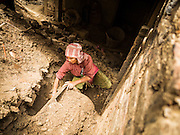 04 AUGUST 2015 - KHOKANA, NEPAL: A woman digs out her family's rice milling machine in their home in Khokana, a village about an hour from Kathmandu. Her husband was injured in the earthquake and can't work so she was digging out the milling machine, that was trapped in their house when it collapsed during the earthquake. The Nepal Earthquake on April 25, 2015, (also known as the Gorkha earthquake) killed more than 9,000 people and injured more than 23,000. It had a magnitude of 7.8. The epicenter was east of the district of Lamjung, and its hypocenter was at a depth of approximately 15 km (9.3 mi). It was the worst natural disaster to strike Nepal since the 1934 Nepal–Bihar earthquake. The earthquake triggered an avalanche on Mount Everest, killing at least 19. The earthquake also set off an avalanche in the Langtang valley, where 250 people were reported missing. Hundreds of thousands of people were made homeless with entire villages flattened across many districts of the country. Centuries-old buildings were destroyed at UNESCO World Heritage sites in the Kathmandu Valley, including some at the Kathmandu Durbar Square, the Patan Durbar Squar, the Bhaktapur Durbar Square, the Changu Narayan Temple and the Swayambhunath Stupa. Geophysicists and other experts had warned for decades that Nepal was vulnerable to a deadly earthquake, particularly because of its geology, urbanization, and architecture.     PHOTO BY JACK KURTZ