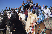 Crowds watch the horse procession pass during the first day of the Kano Durbar Fantasia..The Durbar Fantasia, is the moment where The Husa residents of Kano wear traditional dress, their local leaders and chiefs mount horses, and together with their militias display allegiance and homage to their leader, the Emir of Kano. This takes place after Ramadan. The Emir is Kano's State official political and economic feudal leader, everyone seeks to be in his pleasure, otherwise they reap the consequences..Kano is the largest Muslim Husa city, under the feudal, political and economic rule of the Emir. Kano and the other eleven northern states are under Islamic Sharia Law which is enforced by official state apparatus including military and police, Islamic schools and education, plus various volunteer Militia groups supported financially and politically by the Emir and other business and political bodies. 70% of the population live below the poverty line. Kano, Kano State, Northern Nigeria, Africa