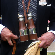A race goer with a vintage pair of binoculars during the race meeting at Royal Ascot Race Course. Royal Ascot is one of the most famous race meetings in the world, frequented by Royalty and punters from the high end of society to the normal everyday working class. Royal Ascot 2009, Ascot, UK, on Thursday, June 18, 2009. Photo Tim Clayton..