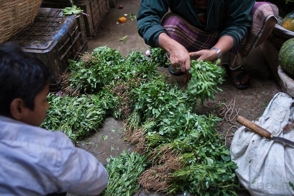 Fresh greens for sale at a farmer's market in Dhaka, Bangladesh.