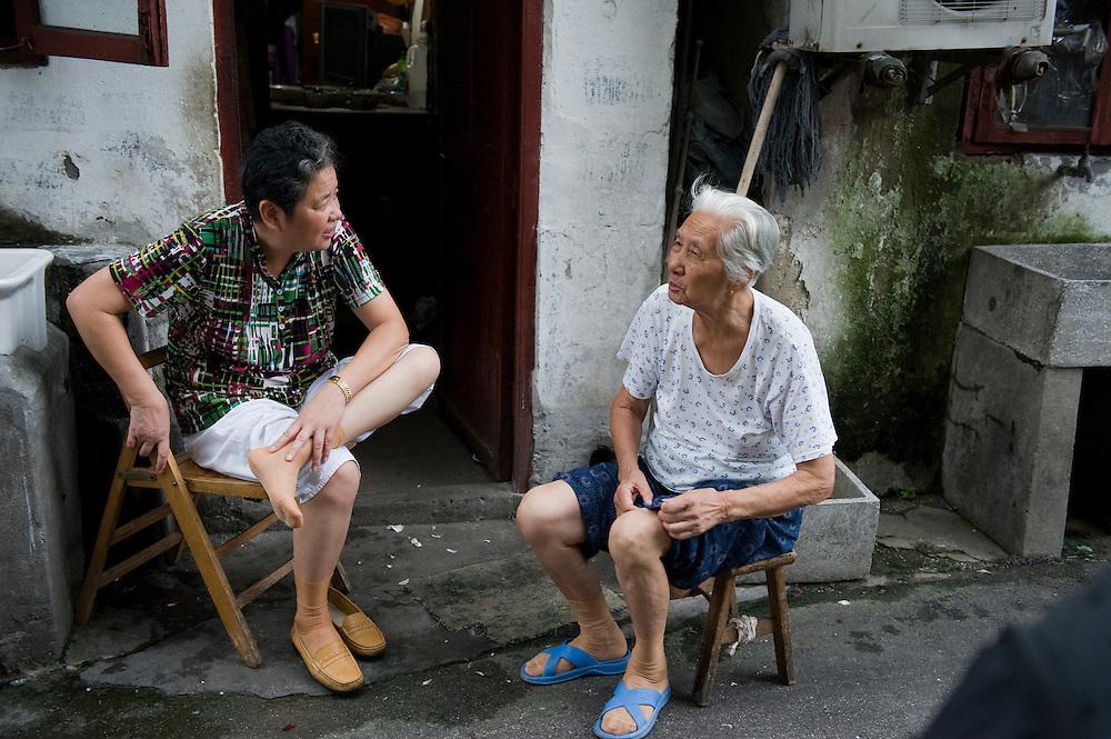 China, Shanghai,  27 aug 2010.Chinese vrouwen. Twee chinese vrouwen, waarvan een een bejaarde vrouw, zitten op straat en brengen de tijd pratend door...Foto (c)  Michiel Wijnbergh