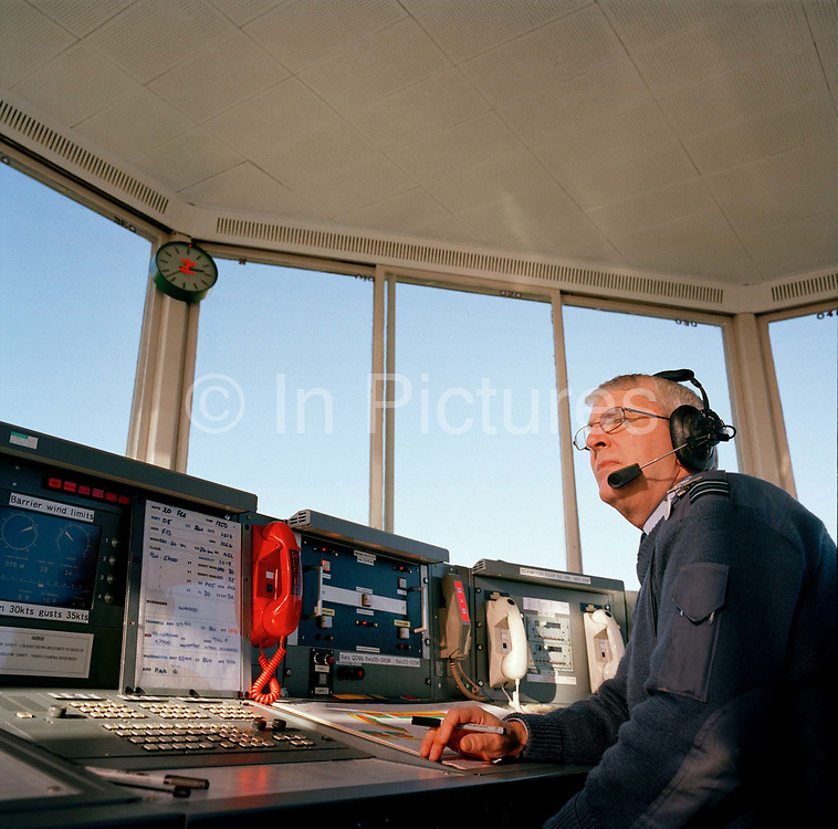Military air traffic controller Flight Lieutenant Barrie Robinson is on duty in the control tower at RAF Scampton, home base of the 'Red Arrows', Britain's Royal Air Force aerobatic team. RAF controllers liaise with civilian air authorities to ensure safe travel for any aircraft using their airspace, manning communications and airfield safety, the officer wears a headset with which to speak to air crew and ground-based personnel. Scampton is not the busy airfield that other stations are where larger squadrons are based but the Red Arrows fly their training sorties from here up to six times a day in the winter months then use this as a base from which to fly their summer air shows.