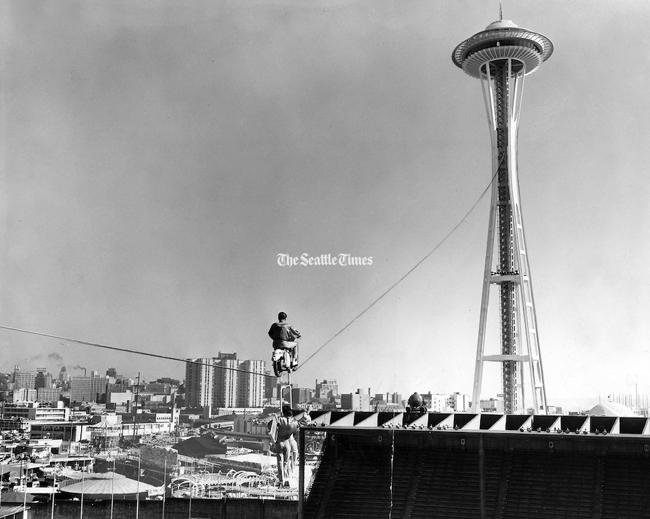 On April 19, 1962 three German high-wire aerialists of the Circus Berlin's Zugspitz ladder act thrilled World's Fair workers by trying out their act high above the fairgrounds on a steel cable they had strung between the roof of the Memorial Stadium and a point 376 feet high on the Space Needle. Siegfried Cimarro, 30, of West Berlin drove a motorcycle with specially grooved wheels on the cable, to a 300-foot height while Rudi Berg, 32, of Essen and Peter Czaya, 25, of West Berlin rode on a steel-pipe stabilizing. (Seattle Times Archive, 1962)