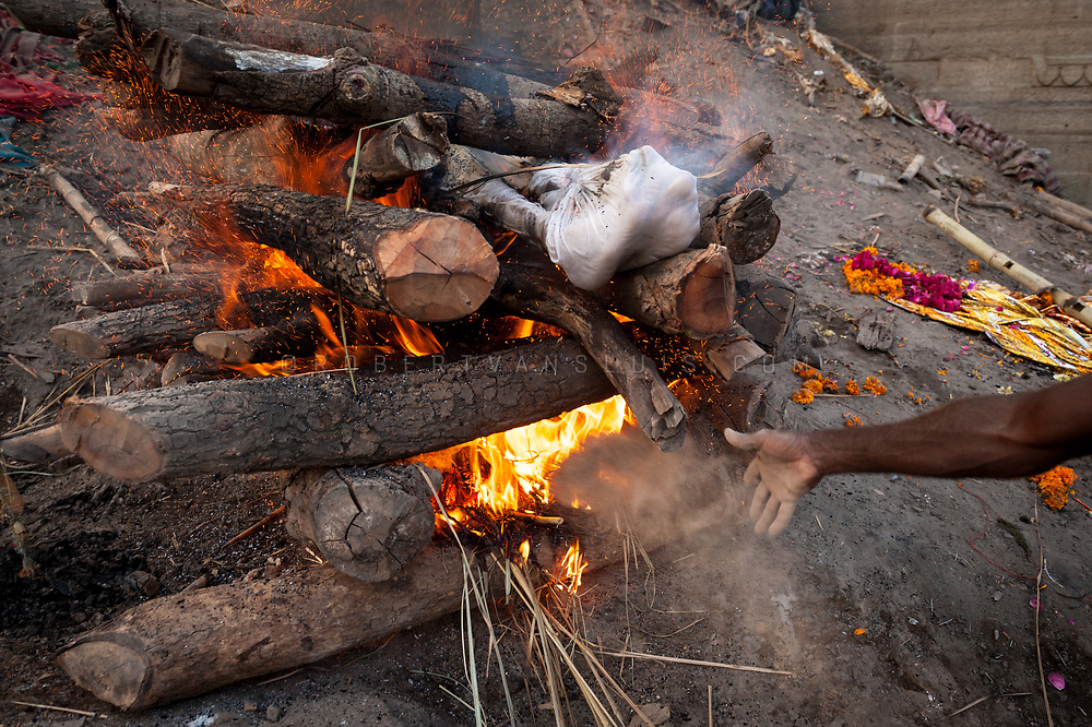 A man throws wood chips into a funeral pyre at Manikarnika cremation ground, Varanasi, India. Photo © robertvansluis.com