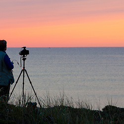 A photographer at the Marconi Station Site at Cape Cod National Seashore in Wellfleet, Massachusetts. Sunrise.