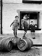 ..Revisit 1950s Ireland with an unforgettable .new collection of photographs from the Lensmen Photographic Archive..The 1950s Ireland in Pictures. ..Picture: Likely lads play on beer barrels in Castlebar 1952.. A unique collection of photographs that captures the essence of an important decade in Irish life and will bring back memories of the people, personalities, events - big and small - that shaped the period...Lensmen, Ireland's premier photographers, captured the essence of life in Ireland during the 1950s in their stunning and thought-provoking images. This new collection of their iconic photographs captures the 1950s in all its grit and glory and offers a fascinating insight into the cultural and political events of the decade. ..Established by Andrew Farren and Padraig MacBrian in 1952, Lensmen grew to become a substantial agency and this year celebrates 60