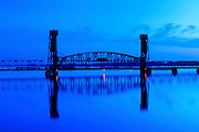 The blue light of dawn illuminates the historic 'Old Southern Railway Bridge', a lift bridge built in 1833 that spans the Tennessee River.  The Norfolk Southern Railway currently owns and operates the bridge.