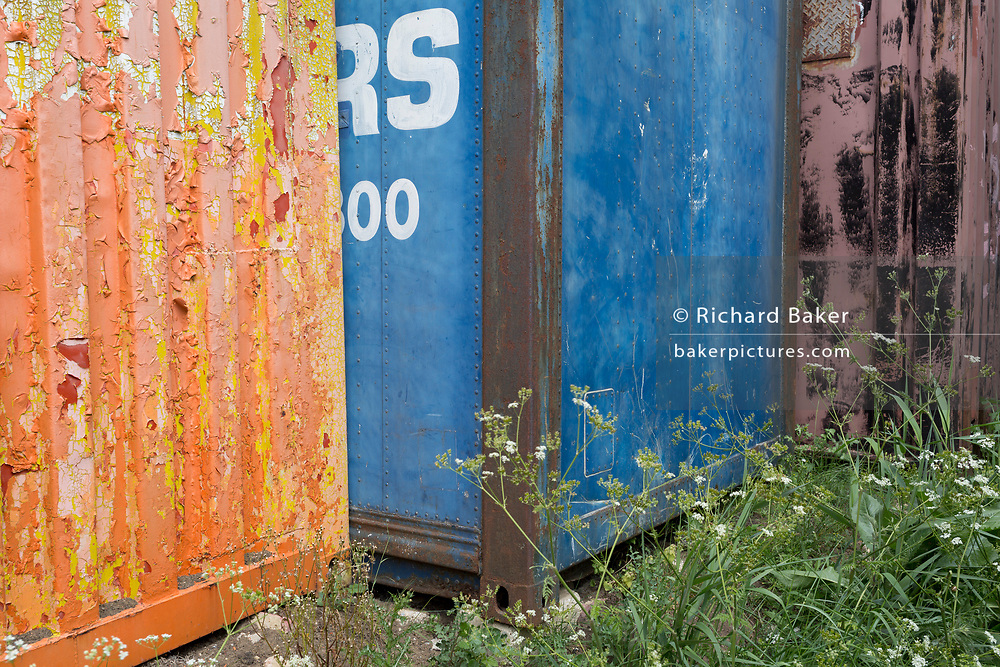 Old shipping container colours and their textures along the on the Saxon Shore Way footpath near Oare, on 29th May 2019, near Faversham, Kent, England.