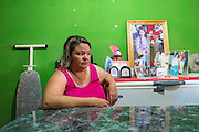 2014/11/18 - Monte Maiz, Argentina: Antónia Alaris (36) sits in her living-room next to an altar in memory to her daughter, Antonella Fuentes, who was diagnosed with osteosarcoma, a cancerous bone tumor, at the age of 6. She died a few months later.  The cases of cancer grew exponentially in the area since the introduction of glyphosate on the soy cultivation.  707 <br /> Cancer cases per 100,000 pepople were register by health researchers in the core area of soybean cultivation. These are three times as many  as the national average. (Eduardo Leal)
