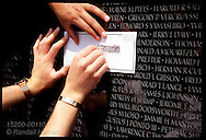 Three hands make rubbing of name engraved in bracelet and on the wall at Vietnam War Memorial Washington, DC