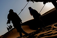 Tourist caravan with camel (dromedary) guides at Erg Chebbi in Merzouga, Sahara desert of Morocco.