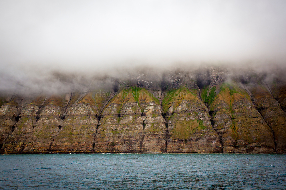 Clouds on seacliffs, on the coast of Isjforden, Svalbard. The cliffs are marked with the signs of coal mining from the 20th century, and the green summer tundra that grows durig the short summer season - which is lengthening due to climate change.