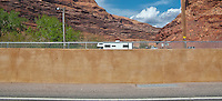 a highway barrier blocks the view of the canyon as US 191 crosses the Colorado River near Moab, Utah panorama
