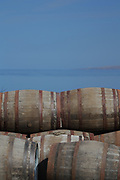 Bunnahabhain Distillery's casks sit in the sunshine in front of The Sound of Islay