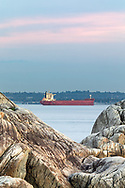 The Bulk Carrier Attikos anchored on English Bay during an early fall evening in Vancouver, British Columbia, Canada.  Photographed from Point Atkinson in Lighthouse Park in West Vancouver with Point Grey (Vancouver) in the background.