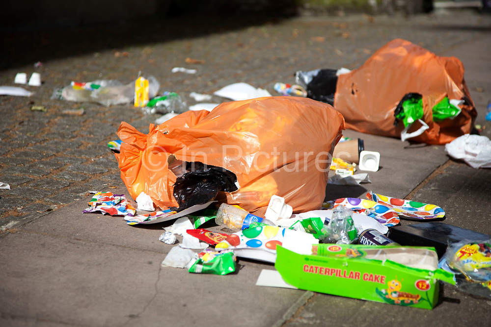 Rubbish on the street. Litter on a large scale next to a bin.