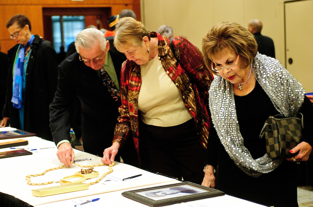 Jo Merlo (right to left) reviews a selection of items available for silent auction with Judy and Leonard Longawa during the second annual Gala for the Cause for Sainthood of Father Augustus Tolton at the Hyatt Regency McCormick Place on Friday, October 19th, 2012. The event is sponsored by The Archdiocese of Chicago's Office for Black Catholics, The Father Tolton Guild and the Office of Vicariate VI and Bishop Joseph Perry l Brian J. Morowczynski~ViaPhotos..For use in a single edition of Catholic New World Publications, Archdiocese of Chicago. Further use and/or distribution may be negotiated separately. ..Contact ViaPhotos at 708-602-0449 or email brian@viaphotos.com.   .The Archdiocese of Chicago's Office for Black Catholics hosts it's second annual Gala for the Cause for Sainthood of Father Augustus Tolton at the Hyatt Regency McCormick Place on Friday, October 19th, 2012. The event is co-sponsored by The Father Tolton Guild and the Office of Vicariate VI and Bishop Joseph Perry.