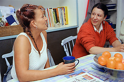 Two women sitting at table in kitchen talking,