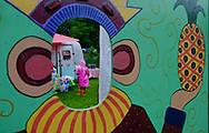 Standing in the rain, a young girl waits for her parents outside of their camper at the Lake Eden Arts Festival in Black Mountain, N.C.