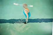 A senior women doing water aerobics in a pool