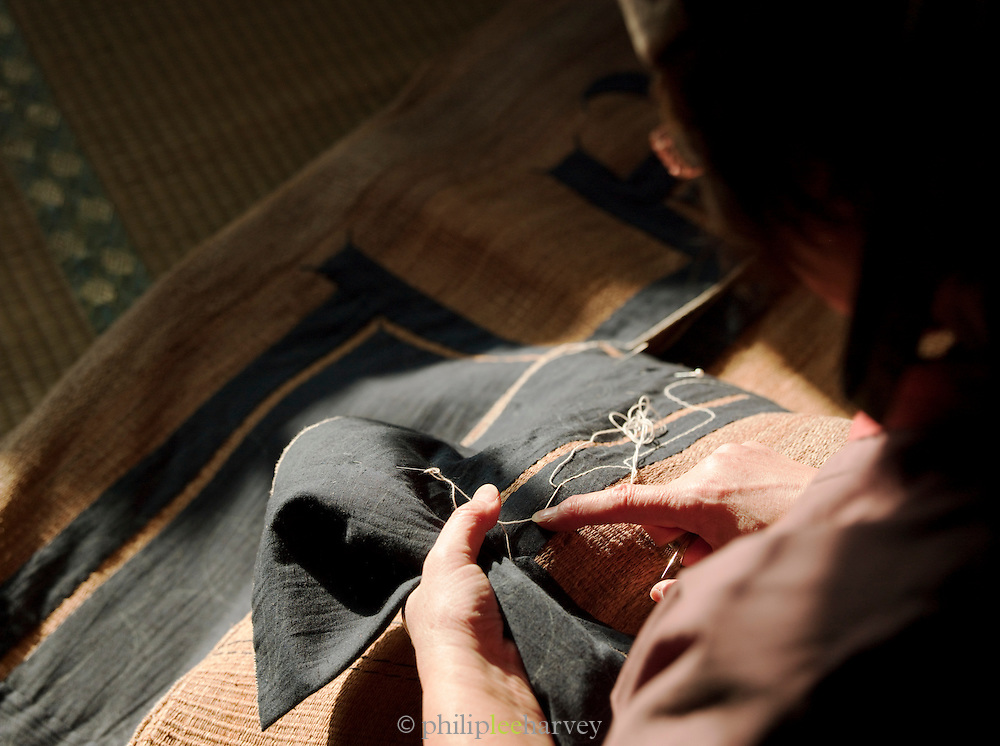 An Ainu woman sewing in a hut at the Ainu Museum at Lake Poroto. The Ainu people are indigenous to Japan and Russia. Hokkaid?, Japan
