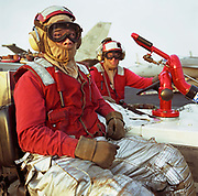 Two crewmen aboard the US Navy aircraft carrier USS Harry S Truman sit on a fire vehicle on the ship's deck. Wearing red signifies that they are part of a crash and salvage team who respond to emergencies and fire hazards and so wear flame-retardant and anti-flash clothing material. Ordinarily they are responsible for making safe and towing ('doing the bow dance') $38 million F/A-18s fighters round the deck of the Navy's newest aircraft carrier, here on coalition patrol somewhere off Kuwait in the Arabian Sea. The Truman is so called after the US President who was in office from 1945 to 1953.  Picture from the 'Plane Pictures' project, a celebration of aviation aesthetics and flying culture, 100 years after the Wright brothers first 12 seconds/120 feet powered flight at Kitty Hawk,1903.
