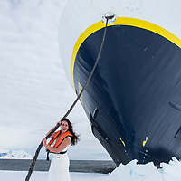 A newlywed bride on ger Honeymoon poses on the fast ice at the bow of the National Geographic Explorer while in Crystal Sound, Antarctica.