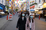 As Londoners await the announcement of a second coronavirus lockdown it's business as usual in the West End with people out and about on what will be the last weekend before a month-long total lockdown, as seen here as people pass wearing face masks on Gerrard Street in Chinatown on 30th October 2020 in London, United Kingdom. The three tier system in the UK has not worked sufficiently, to suppress the virus, and there have have been calls by politicians for a 'circuit breaker' complete lockdown to be announced to help the growing spread of the Covid-19.