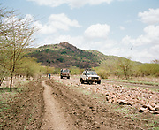 """NUBA MOUNTAINS, SUDAN – JUNE 9, 2018: Aid workers travel from the Yida host community across the Sudan border and through SPLA/M-N controlled territory to reach the Nuba Mountains. <br /> <br /> In 2011, the government of Sudan expelled all humanitarian groups from the country's Nuba Mountains. Since then, the Antonov aircraft has terrorized the Nuba people, dropping more than 4,080 bombs on hospitals, schools, marketplaces and churches. Today, vestiges of the Antonov riddle the landscapes of daily life, where more than 1 million Nuba live in famine conditions – quietly enduring the humanitarian blockade intended to drive them out of the region. The skies are mostly clear. Yet the collective memory of the bombings remains an open wound, and the Antonov itself a persistent threat. So frequent were the attacks that the Nuba nicknamed the high flying aircraft and its dismal hum: """"Gafal-nia ja,"""" they would declare, running to the hillsides. """"The loss of appetite has come."""""""