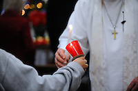 Pastor Jim Luther passes the flame In a Christmas Eve candlelight service at the United Methodist Church in Salinas.