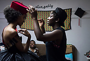 Designer Jacqueline Addison, right, owner of Akua Gabby, adds a hat to one of her styles on model Lydia Negussie during a fitting at Addison's studio. Seated on the couch is Black Fashion Week founder Natalie Morrow.