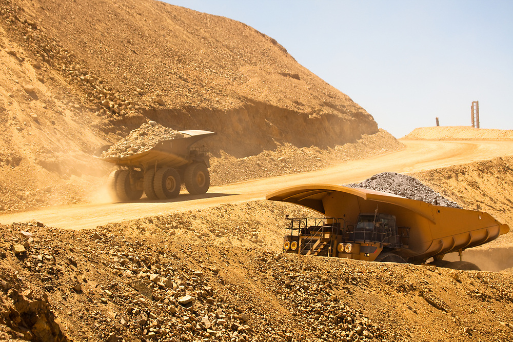Huge dump trucks loaded with mineral  in a copper mine in Chile.