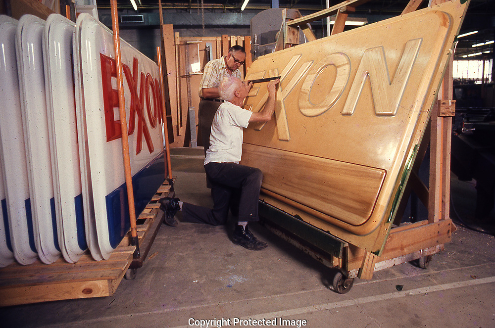 Before the mold for making the plastic sign, a model has to be made. .  Workers at a sign factory in Denton, Maryland inspect the wood mold for the new Exxon signs in 1972<br /><br />Photograph ny Dennis Brack. bb78