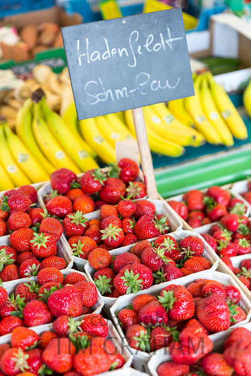 Strawberries and bananas in display of fruits at food market in Lubeck, Northern Germany