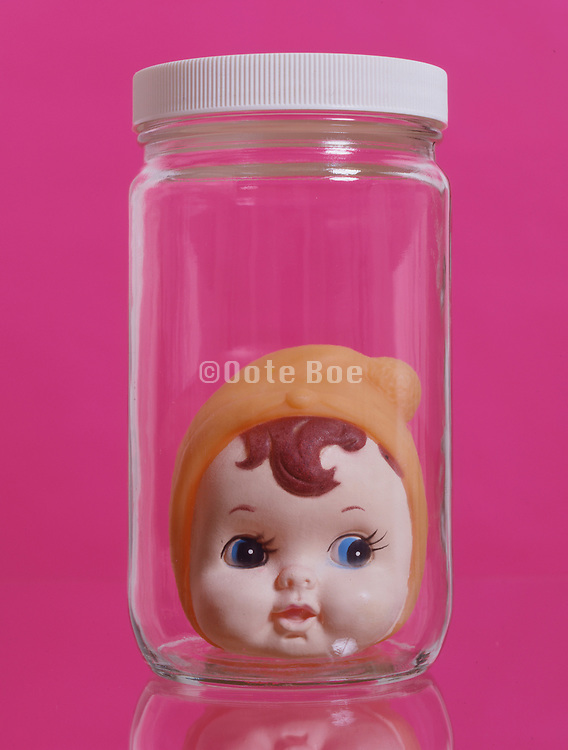 plastic doll head in glass jar against a pink background.