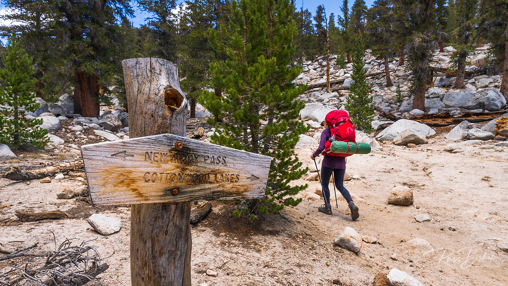Backpacker and trail sign on the Cottonwood Lakes Trail, John Muir Wilderness, California USA