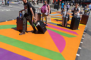 A travel family push their wheelie suitcases over the multi-coloured markings of a crossing at Piccadilly Circus, on 16th July 2021, in London, England.