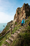 Woman enjoying a healthy lifestyle, walking on the steps and cliff paths on the south coast of Jersey, Channel Islands
