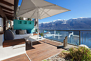 Terrace lounge with comfortable divans and lake view in a luxury house
