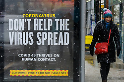 "© Licensed to London News Pictures. 24/01/2021. London, UK. A woman walks past the government's 'Don't Help The Virus Spread' publicity campaign poster in north London during snowfall in the capital. The Health Secretary, Matt Hancock urges the public to continue to follow the lockdown restrictions and stay at home as case numbers are ""incredibly high"" and the NHS remains under intense pressure. Photo credit: Dinendra Haria/LNP"
