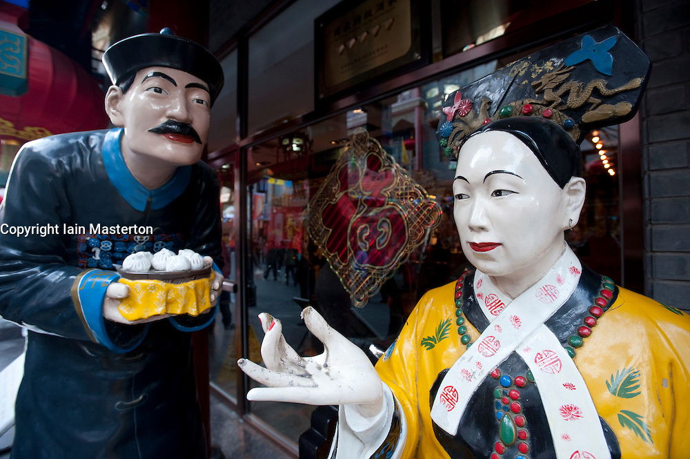 Male and female statues in Imperial clothing stand outside a dumpling restaurant in central Beijing