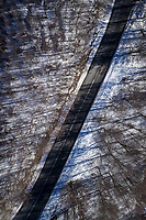 Aerial view of a road in the forest surrounded by snow.