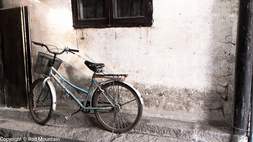Bicycle parked at the side of an old building in China