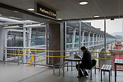 As the Coronavirus pandemic spreads across the UK, businesses and entertainment venues not already closed with the threat of job losses, struggle to stay open with growing rumours of a lockdown and travel restrictions around the capital. Londoners start to work from home but one traveller reads at a deserted Blackfriars railway station that overlooks the river Thames, on 19th March 2020, in London, England.
