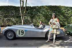 **CAPTION CORRECTION. Picture originally sent with wrong date. Picture was taken TODAY 11/09/2015** © licensed to London News Pictures. 11/09/2015<br /> Goodwood Revival Weekend, Goodwood, West Sussex. UK.<br /> The Goodwood Revival is the world's largest historic motor racing event. Competitors and enthusiasts dress in period fashions recreating the glorious days of the race circuit.<br /> Pictured Karin Johnston from Sydney in a period dress poses next to a Classic Jaguar XK120.<br /> <br /> Photo credit : Ian Whittaker/LNP